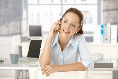 Het jonge vrouwelijke babbelen op mobiele zitting in bureau Stock Foto