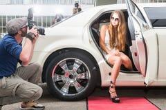 Het jonge vrouwelijke beroemdheid stellen in limousine voor paparazzi op rood royalty-vrije stock foto's
