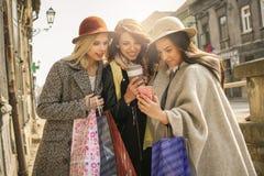 Het jonge vrouwelijke beste vrienden doen die op de straten winkelen U Stock Foto's