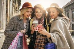 Het jonge vrouwelijke beste vrienden doen die op de straten winkelen U Royalty-vrije Stock Foto