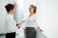 Het jonge vrouwelijke ceo stootkussen van de holdingsaanraking terwijl het spreken met haar partner in modern bureaubinnenland ti Stock Foto