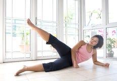 Het jonge vrouwelijke doende been heft als deel van oefening op Royalty-vrije Stock Afbeelding