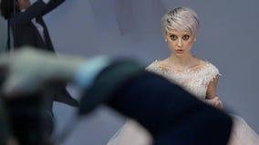 Het jonge vrouwelijke model stelt en glimlacht tijdens photoshoot Actietijd Het blonde model stelt en glimlacht stock video