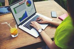 Het jonge vrouwelijke ondernemerswerk met statistieken gegevens en het analyseren van prestaties stock foto's