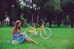 Het jonge vrouwelijke ontspannen op een groen gras met fiets in een park op een zonnige dag royalty-vrije stock foto