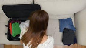 Het jonge vrouwelijke reiziger meeslepen om kleren in reis te zetten doet bang om vlucht niet te verliezen in zakken stock footage
