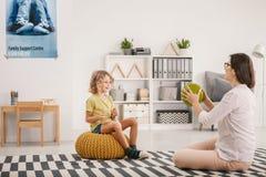 Het jonge vrouwelijke therapeut spelen met een gelukkige ouderloze jongen tijdens royalty-vrije stock afbeeldingen