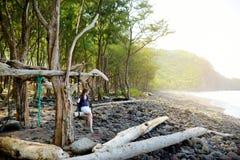 Het jonge vrouwelijke toerist ontspannen op een met de hand gemaakte schommeling op rotsachtig strand van Pololu-Vallei op Groot  Stock Foto's