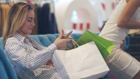 Het jonge vrouwen eindigen onderzoekt het winkelen zakken in wandelgalerij stock videobeelden