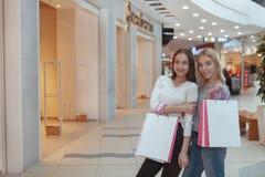 Het jonge vrouwen genieten die samen bij de wandelgalerij winkelen stock afbeelding