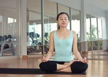 Het jonge vrouwen mediteren, die bij de gymnastiek ontspannen stock afbeeldingen