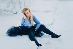 Het jonge vrouwenblonde in zwarte sapagah zit in de sneeuw royalty-vrije stock afbeeldingen