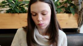 Het jonge vrouwenbrunette eet broodje door houten stokken Het gezicht van de close-up stock video
