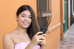 Het jonge vrouwenholding cellphone en denken stock foto's