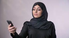 Het jonge weet moslimmeisje in hijab maakt selfie op haar smartphone, horlogefoto's, communicatie godsdienstig concept,
