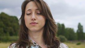 Het jonge wijfje bevindt zich met in openlucht gesloten ogen, rond voelend en wereld stock video