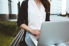 Het jonge wijfje die freelancer arbeidsmarktonderzoek naar moderne laptop maken, zit in openlucht in stedelijke straat royalty-vrije stock afbeeldingen
