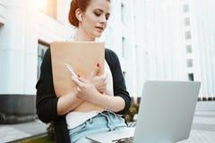 Het jonge wijfje die freelancer arbeidsmarktonderzoek naar moderne laptop maken, zit in openlucht in stedelijke straat Het studen royalty-vrije stock fotografie