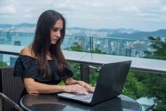 Het jonge wijfje freelancer kleedde zich in het zwarte werken aan een projectlaptop computer terwijl het zitten bij het terras va Royalty-vrije Stock Foto's