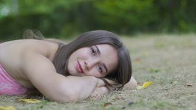 Het jonge wijfje ligt in park kijkt in camera, overweegt de dromende vrouw op gras stock video