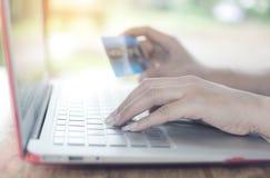 Het jonge wijfje maakt een aankoop op Internet van laptop B online royalty-vrije stock afbeeldingen