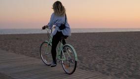 Het jonge wijfje van de blondefotograaf berijdt fiets op het strand stock videobeelden