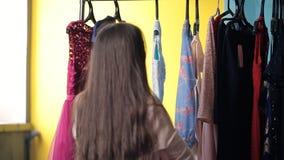 Het jonge wijfje werkt in kleedkamer kiezend kleding stock videobeelden