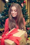 Het jonge wijfje zit voor de Kerstmisboom en heeft giftdoos met rood lint in haar handen Stock Foto's