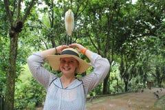 Het jonge witte meisje op van wie hoed de veeaigrette zich bevindt is de talrijkste vogel van de reigerfamilie stock fotografie