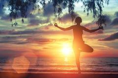 Het jonge yogameisje praktizeren op het oceaanstrand bij verbazende mooie zonsondergang nave Stock Fotografie