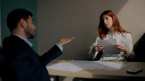 Het jonge zakenlui bespreekt zaken, zittend bij lijst in werkplaats in bedrijf stock video