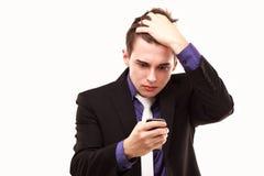Het jonge zakenman amazedlylooking bij de telefoon Stock Afbeelding