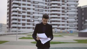 Het jonge zakenman lopen en gooit documenten tegen bedrijfs de bouwachtergrond weg stock footage