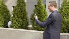 Het jonge zakenman lopen onderaan de straat en schrijft een bericht op smartphone stock video