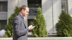 Het jonge zakenman lopen onderaan de straat en schrijft een bericht op smartphone stock videobeelden