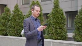 Het jonge zakenman lopen onderaan de straat met draadloze oortelefoons en schrijft een bericht op smartphone stock video
