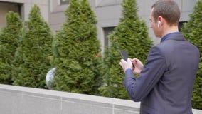 Het jonge zakenman lopen onderaan de straat met draadloze oortelefoons en schrijft een bericht op smartphone stock videobeelden