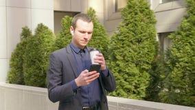 Het jonge zakenman lopen onderaan de straat met draadloze oortelefoons in de oren en schrijft een bericht op de telefoon stock video