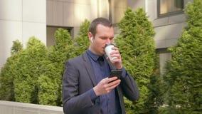 Het jonge zakenman lopen onderaan de straat met draadloze oortelefoons in de oren en schrijft een bericht op de telefoon stock videobeelden