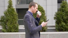 Het jonge zakenman lopen onderaan de straat met draadloze oortelefoons in de oren en schrijft een bericht op de telefoon stock footage