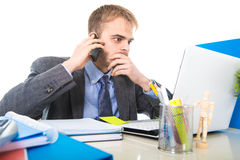 Het jonge zakenman ongerust gemaakte vermoeide spreken op mobiele telefoon in bureau die aan spanning lijden stock afbeelding