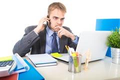 Het jonge zakenman ongerust gemaakte vermoeide spreken op mobiele telefoon in bureau die aan spanning lijden stock foto