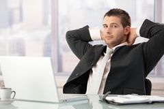 Het jonge zakenman ontspannen in bureau Royalty-vrije Stock Foto's