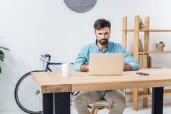 Het jonge zakenman typen op laptop bij werkplaats in bureau Royalty-vrije Stock Afbeeldingen