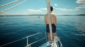 Het jonge Zeeman ontspannen op het jacht van de vakantiezeilboot stock videobeelden