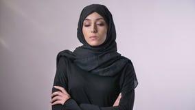 Het jonge zekere moslimmeisje in hijab kruist wapens, lettend op bij camera, godsdienstig concept, grijze achtergrond