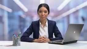 Het jonge zelfverzekerde businesslady kijken aan camera en slow-motion glimlachen, stock videobeelden