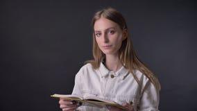 Het jonge zoete meisje leest boek, lettend op bij camera, het glimlachen, grijze achtergrond stock videobeelden