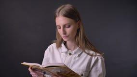 Het jonge zoete meisje leest boek, lettend op bij camera, grijze achtergrond stock footage