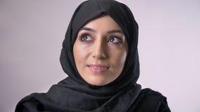 Het jonge zoete moslimmeisje in hijab let op bij camera, het dromen concept, godsdienstig concept, grijze achtergrond stock footage